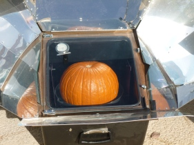 Whole pumpkin baking in a solar oven